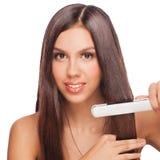 Mujer con el pelo que endereza los hierros Imagen de archivo