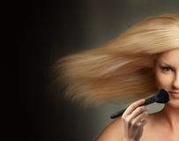 Mujer con el pelo que sopla y con el cepillo del maquillaje Imágenes de archivo libres de regalías