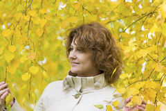 Mujer con el pelo rizado cerca del abedul del otoño Foto de archivo