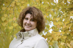 Mujer con el pelo rizado cerca del abedul del otoño Foto de archivo libre de regalías