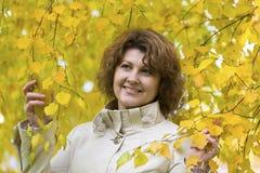 Mujer con el pelo rizado cerca del abedul del otoño Fotos de archivo