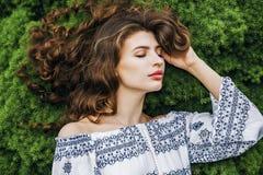 Mujer con el pelo rizado largo que miente en hierba de la primavera Fotografía de archivo libre de regalías