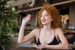 Mujer con el pelo rizado que se sienta en la tabla en restaurante Imagen de archivo libre de regalías