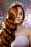 Mujer con el pelo rojo largo en la corona del vestido del lux, ligh de la princesa de la reina foto de archivo libre de regalías