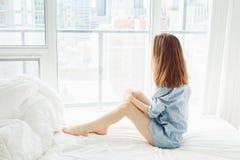 Mujer con el pelo rojo largo que se sienta en cama por la ventana con la opinión de la ciudad, estirando después de despertar Imagenes de archivo