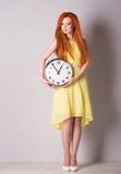 Mujer con el pelo rojo que sostiene un reloj grande Imagen de archivo