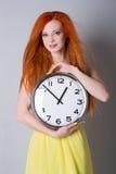 Mujer con el pelo rojo que sostiene un reloj grande Fotos de archivo