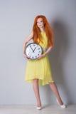 Mujer con el pelo rojo que sostiene un reloj grande Foto de archivo