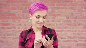 Mujer con el pelo rosado usando un teléfono contra la pared de ladrillo metrajes