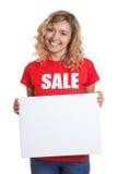 Mujer con el pelo rubio en una camisa de la venta que sostiene un letrero Fotos de archivo libres de regalías
