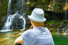 Mujer con el pelo rubio y el sombrero blanco que miran, sentándose y relajándose foto de archivo libre de regalías