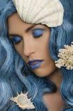 Mujer con el pelo y las conchas marinas azules Fotos de archivo