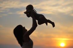 Mujer con el pequeño bebé como silueta Fotografía de archivo