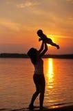 Mujer con el pequeño bebé como silueta por el agua Fotos de archivo