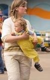 Mujer con el pequeño hijo rizado en pantalones amarillos Foto de archivo