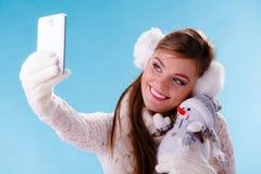 Mujer con el pequeño muñeco de nieve que toma la foto del selfie Fotos de archivo