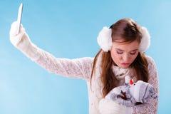 Mujer con el pequeño muñeco de nieve que toma la foto del selfie Foto de archivo libre de regalías