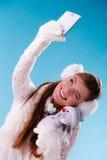 Mujer con el pequeño muñeco de nieve que toma la foto del selfie Imagenes de archivo