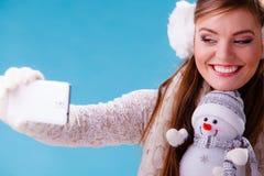 Mujer con el pequeño muñeco de nieve que toma la foto del selfie Imágenes de archivo libres de regalías