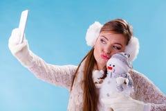 Mujer con el pequeño muñeco de nieve que toma la foto del selfie Imagen de archivo