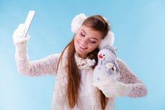 Mujer con el pequeño muñeco de nieve que toma la foto del selfie Fotos de archivo libres de regalías