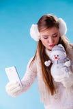 Mujer con el pequeño muñeco de nieve que toma la foto del selfie Fotografía de archivo