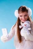 Mujer con el pequeño muñeco de nieve que toma la foto del selfie Foto de archivo