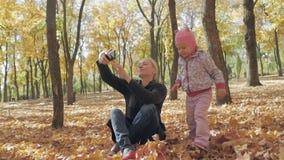 Mujer con el pequeño selfie de la toma de la hija en parque de la ciudad del otoño metrajes