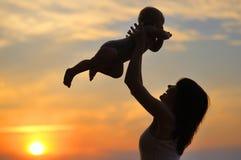 Mujer con el pequeño bebé como silueta Imagen de archivo libre de regalías