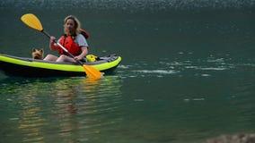 Mujer con el perro en el kajak en el viaje del lago almacen de video