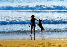 Mujer con el perro en la playa Imágenes de archivo libres de regalías