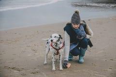 Mujer con el perro en una playa del invierno Imagen de archivo