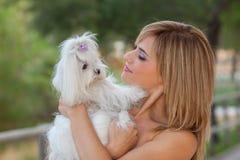 Mujer con el perro maltés del animal doméstico de la familia fotos de archivo libres de regalías