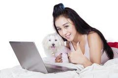 Mujer con el perro maltés que muestra el pulgar para arriba Fotos de archivo