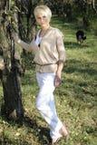 Mujer con el perro que recorre en fondo Fotografía de archivo libre de regalías