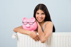 Mujer con el piggybank y el radiador Foto de archivo