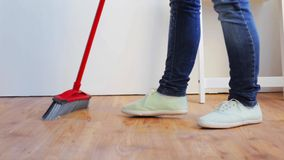 Mujer con el piso de la limpieza de la escoba en casa almacen de metraje de vídeo