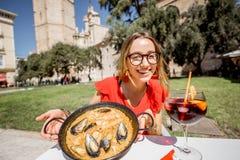 Mujer con el plato de la paella en Valencia fotografía de archivo