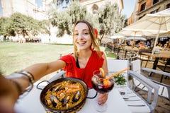 Mujer con el plato de la paella en Valencia foto de archivo