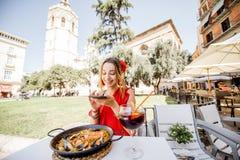 Mujer con el plato de la paella en Valencia fotos de archivo