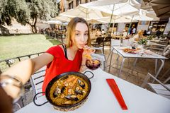 Mujer con el plato de la paella en Valencia fotografía de archivo libre de regalías