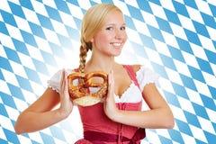 Mujer con el pretzel en un dirndl Imagen de archivo libre de regalías