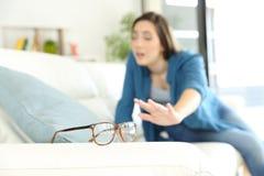 Mujer con el problema de la vista que busca las lentes foto de archivo