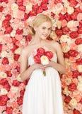 Mujer con el ramo y fondo por completo de rosas Imagen de archivo