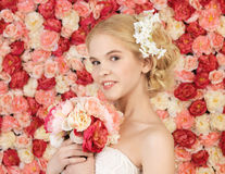 Mujer con el ramo y fondo por completo de rosas Fotografía de archivo libre de regalías