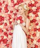 Mujer con el ramo y fondo por completo de rosas Imagenes de archivo