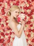 Mujer con el ramo y fondo por completo de rosas Fotografía de archivo