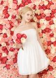 Mujer con el ramo y fondo por completo de rosas Fotos de archivo