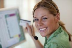 Mujer con el receptor de cabeza y de la tarjeta de crédito jovenes Imágenes de archivo libres de regalías
