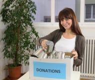 Mujer con el rectángulo de la donación del alimento Imagen de archivo libre de regalías